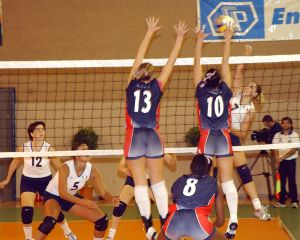 A competitive game of volleyballbeing played by talented women.