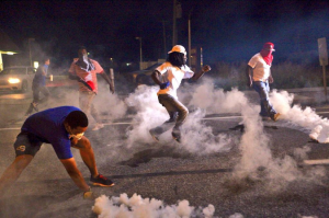 Ferguson rioters act out in defense of Michael Brown.